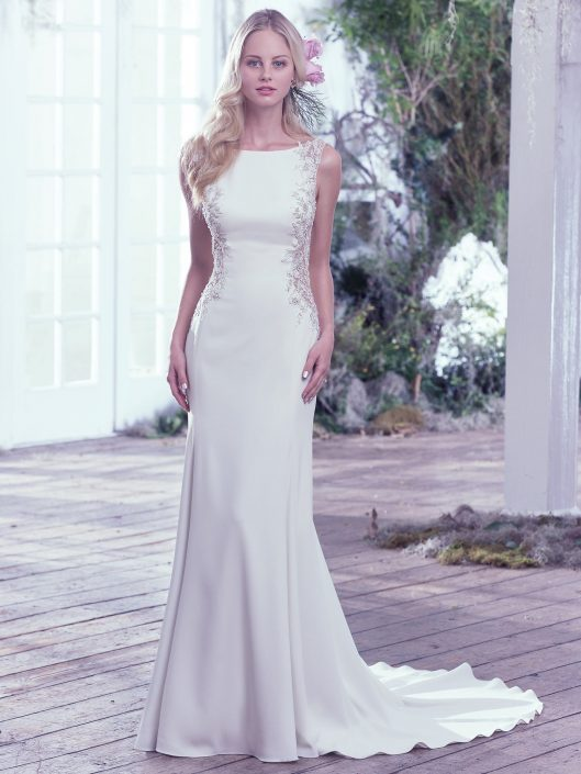 A scoop back is accented with an illusion closure creating a sexy keyhole below the natural waist in this simple wedding gown. Artfully placed lace embellishments featuring Swarovski crystals adorn each illusion side panel adding a modern twist to this Yolivia Crepe satin sheath wedding dress with high bateau neckline. Finished with a zipper closure.