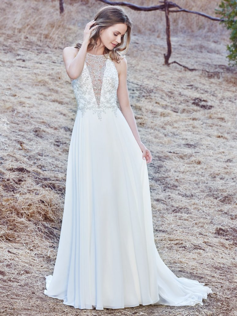This sleeveless sheath wedding gown features a bodice accented in Swarovski crystals and delicate beading, creating an illusion jewel over deep V-neckline and illusion open back. A Revina Chiffon skirt completes the elegant romance of this look. Finished with crystal buttons over zipper closure.