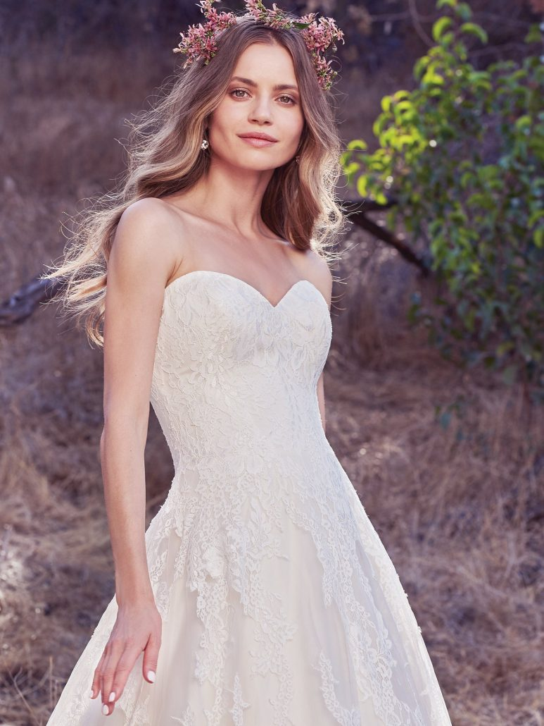 Cascades of breathtaking lace motifs elevate this timeless A-line wedding dress, featuring a subtle sweetheart neckline and a scalloped lace hem. Finished with covered buttons over zipper and inner corset closure.