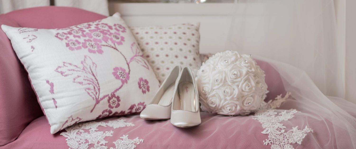 Photo of a pair of bridal shoes and a bouquet of white flowers arrange on a pink chaise lounge with cushions