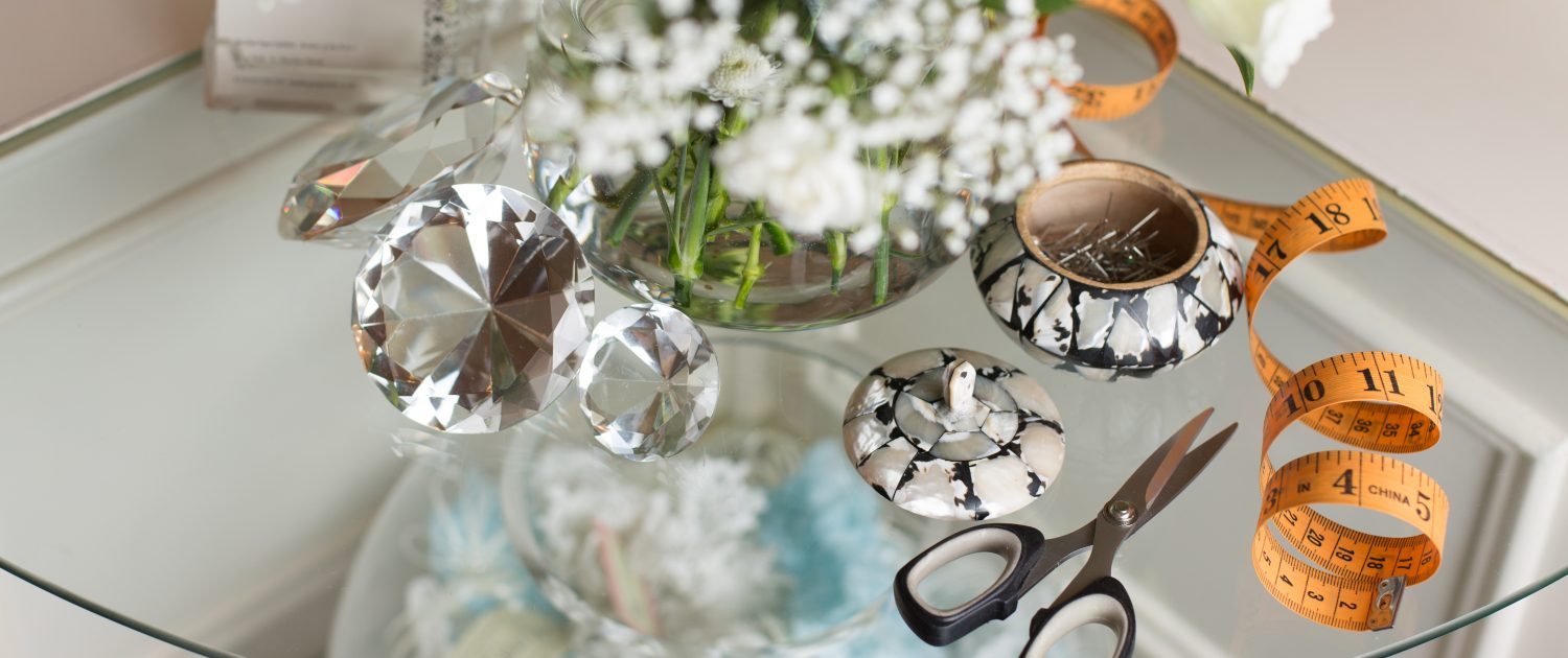 A photo of Wedding dressmakers pins, scissors and measuring tape arrange on a glass table with white flowers and crystals
