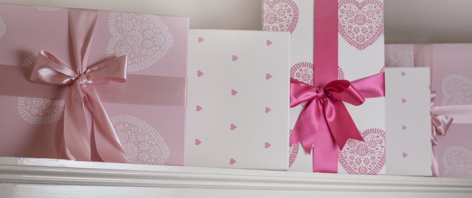 A photo of beautifully wrapped wedding presents in pinks and white with beautiful bows tied in ribbons