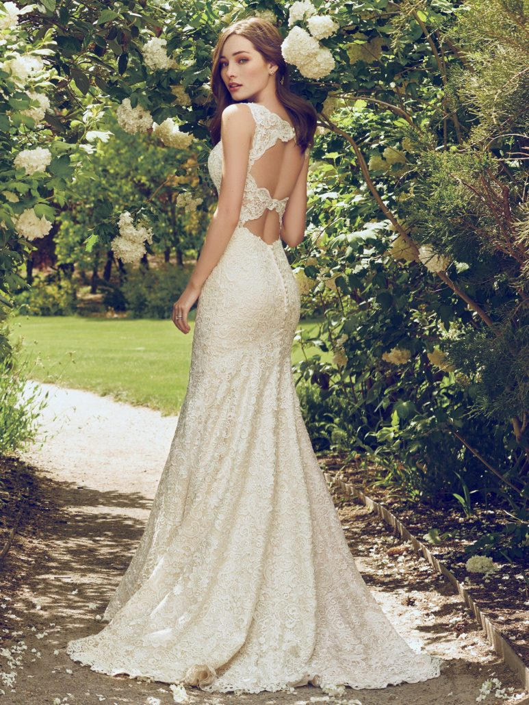 Romantic and vintage-inspired, this allover-lace fit-and-flare features an illusion plunging neckline and scalloped edging. A double-keyhole back adds a touch of alluring elegance to this lace wedding dress. Finished with covered buttons over zipper closure.