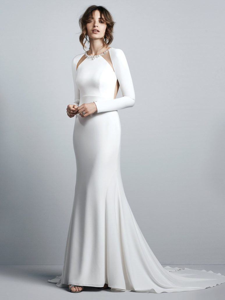 This Talin Stretch Crepe wedding dress evokes Old Hollywood glamour, featuring long sleeves and an illusion open back accented in beading and Swarovski crystals. Illusion cutouts at the embellished jewel neckline complete this sexy yet elegant sheath. Finished with crystal buttons trailing down the train over zipper closure.