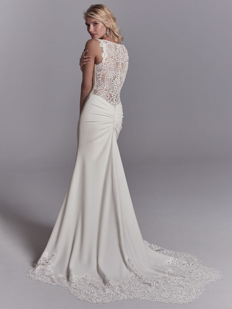 Exquisite lace motifs accent the illusion cutout train, straps, and illusion plunging back in this Chardon Crepe wedding dress. Complete with bateau neckline. Finished with covered buttons and back ruching along zipper closure.