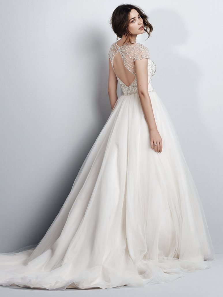 Vintage-inspired beading and Swarovski crystals dance over the bodice of this tulle ballgown wedding dress, completing the illusion jewel over sweetheart neckline, illusion cap-sleeves, and illusion back with keyhole cutout. Finished with crystal buttons over zipper closure.