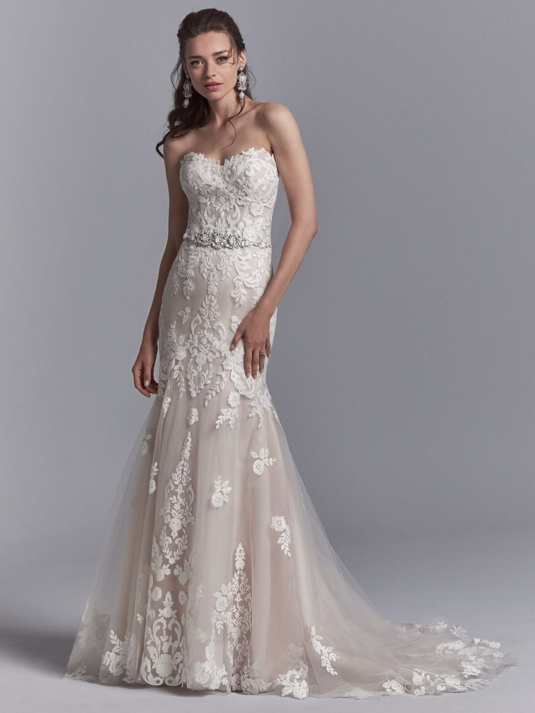 Romantic lace motifs dance over tulle in this fit-and-flare wedding dress, featuring a beaded belt accented in Swarovski crystals, a strapless sweetheart neckline, and illusion scoop back with exposed boning accented in lace motifs. Finished with crystal buttons over zipper closure.