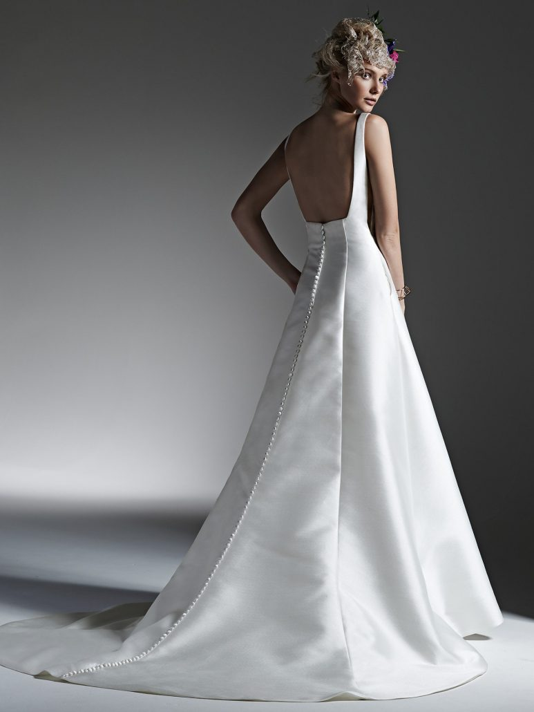 Luxe Reena Mikado creates this dramatic, structured A-line wedding dress with sophisticated bateau neckline, scene-stealing sheer panel inset at side seams, hidden pockets, and stunning open back. Finished with covered buttons over zipper closure.