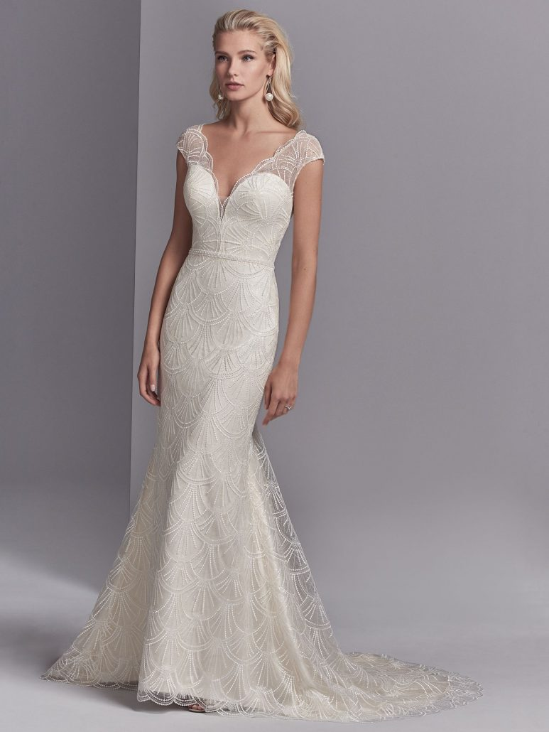 This chic, sheath wedding dress features a tulle overlay of lace motifs accented in clear sequins creating illusion cap-sleeves, an illusion V-over plunging sweetheart neckline, and an illusion V-back. A delicately beaded belt and subtle ruching along the closure completes this vintage-inspired wedding gown. Finished with covered buttons over zipper closure.