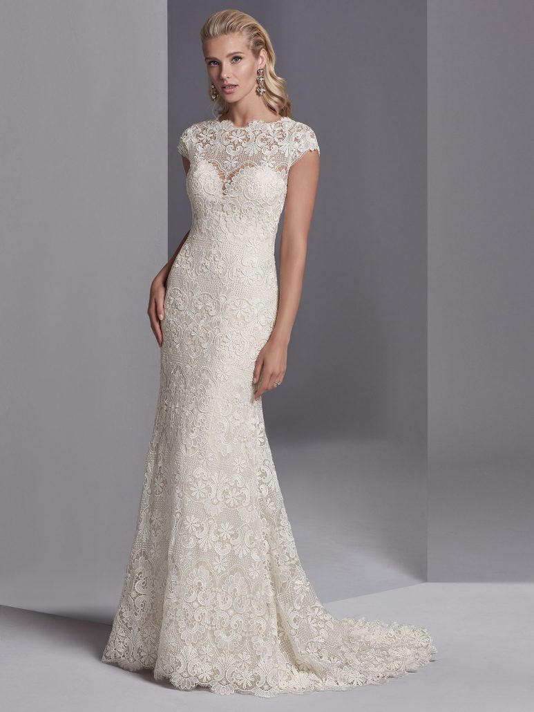 This boho wedding gown features allover lace motifs in a sheath silhouette, with sheer lace comprising the jewel over sweetheart neckline, cap-sleeves, and scoop back. Finished with covered buttons over zipper closure.